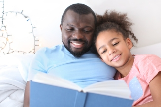 African American man reading bedtime story to his daughter in bed